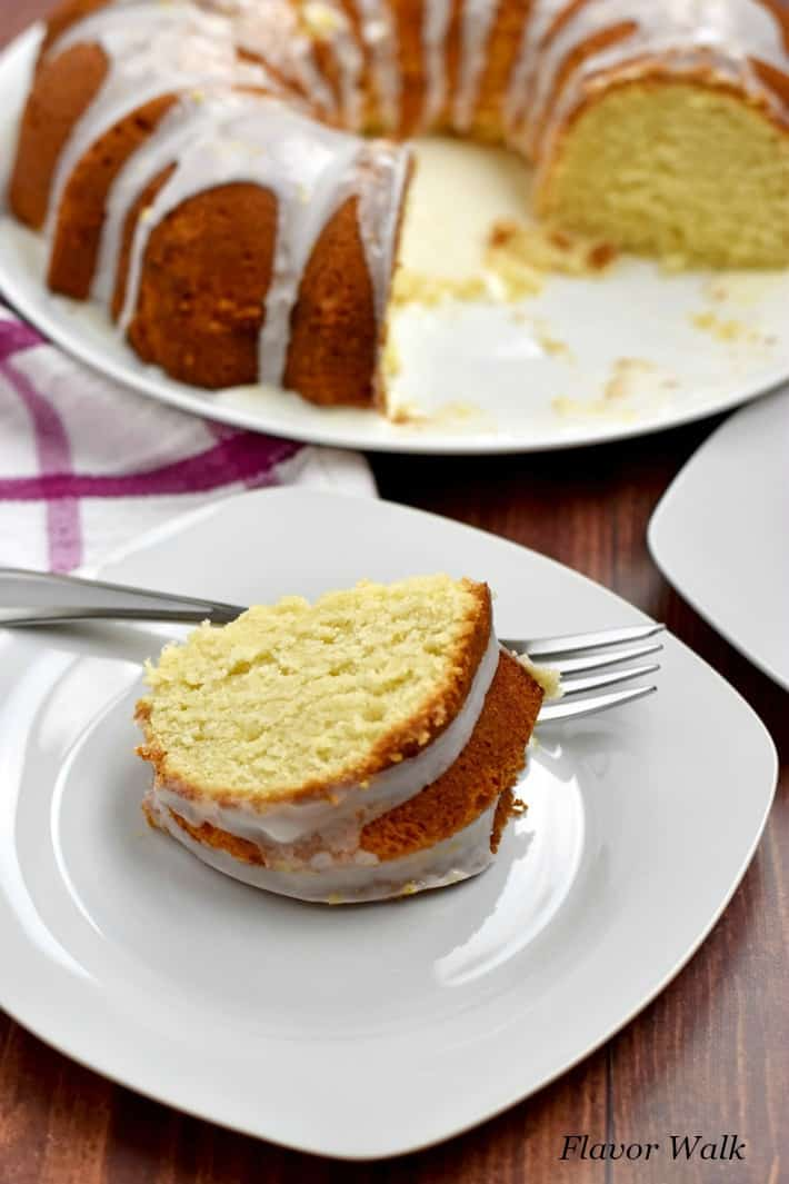A slice of gluten free lemon cake and fork on small white plate with remaining cake in the background.
