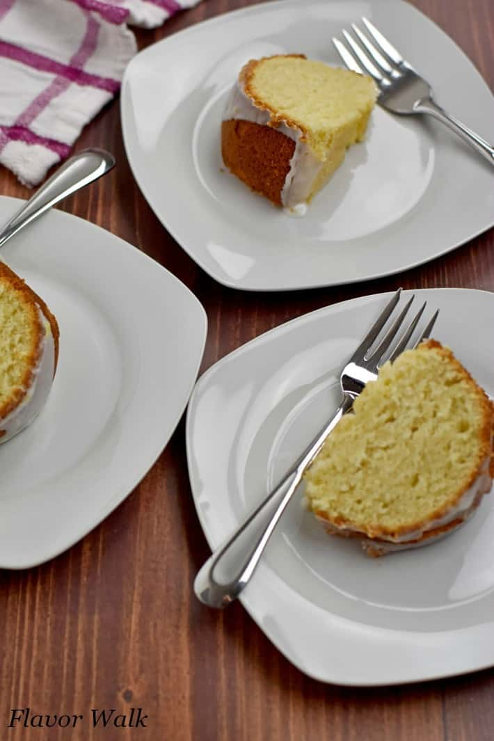 Overhead view of 3 small white plates with forks and slices of gluten free lemon cake.
