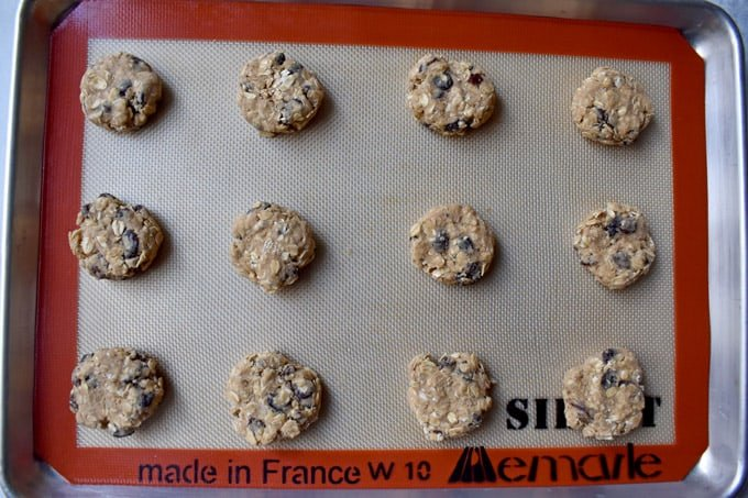 Overhead view of gluten free oatmeal raisin cookie dough balls on silicone lined baking pan.