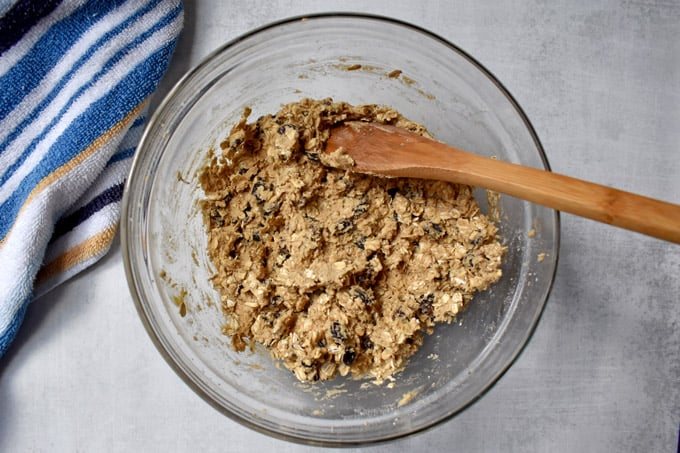 Overhead view of gluten free oatmeal raisin cookie dough and wooden spoon in glass mixing bowl.