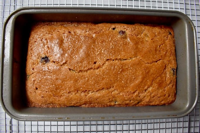 Overhead view of baked gluten free banana blueberry bread in loaf pan cooling on wire rack.