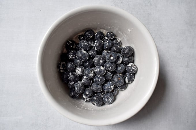 Overhead view of white bowl containing blueberries coated in gluten free flour.