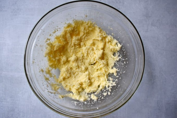 Overhead view of glass mixing bowl containing butter and sugar that was creamed together.