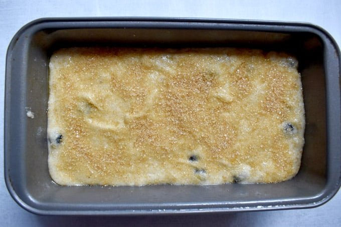 Overhead view of gluten free banana blueberry bread batter in loaf pan.