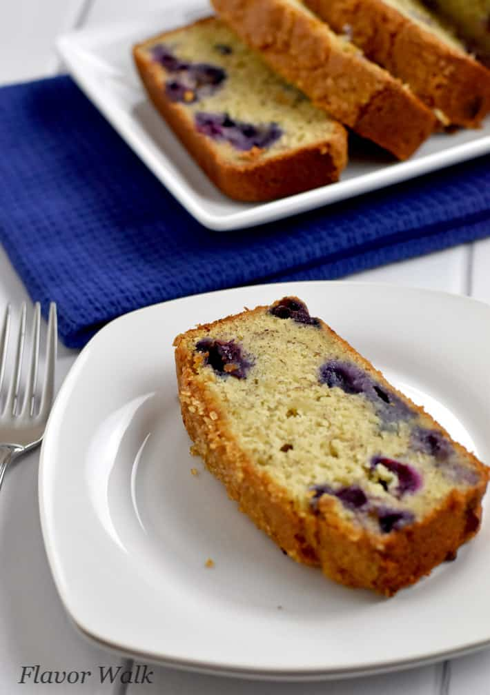 Slice of gluten free banana blueberry bread on stack of two white plates with remaining loaf in the background.