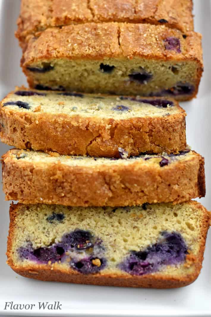 Overhead view of sliced gluten free banana blueberry bread on white plate.