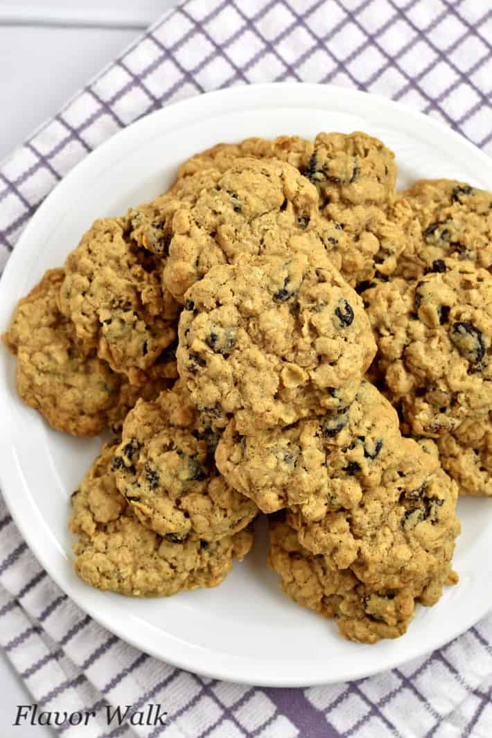 Overhead view of gluten free oatmeal raisin cookies on round white plate with purple and white striped kitchen towel underneath.