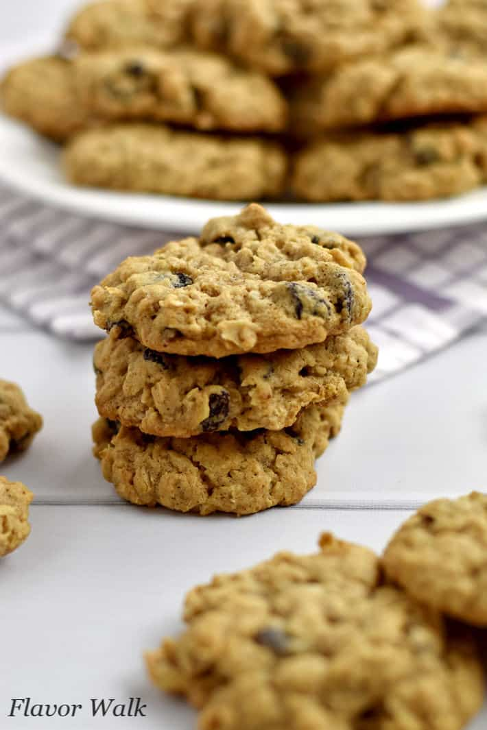 Stack of 3 gluten free oatmeal raisin cookies with more cookies in the foreground and background