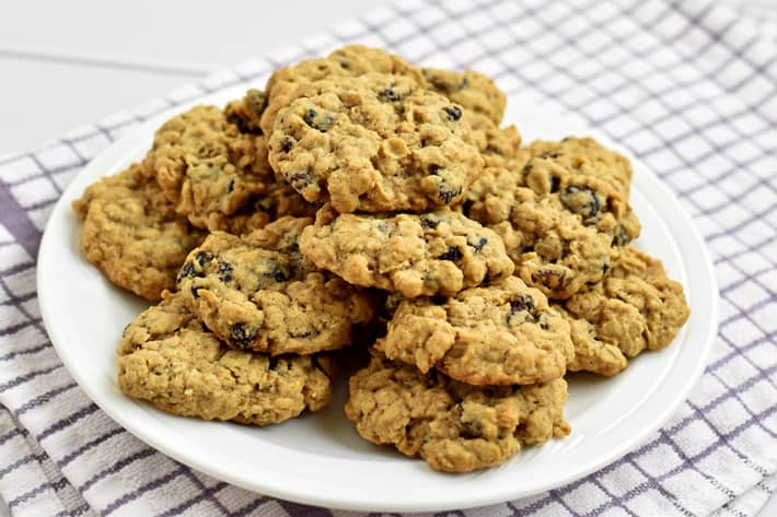 Stack of Gluten Free Oatmeal Raisin Cookies on round white plate with purple and white striped kitchen towel underneath.