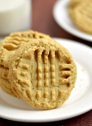 Stack of four gluten free peanut butter cookies on a small white plate with a glass of milk and more cookies in the background.