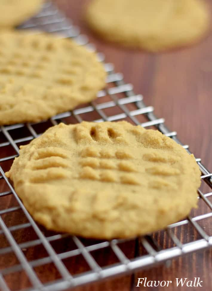 Two gluten free peanut butter cookies on a wire cooling rack with additional cookies in the background.
