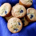 A basket, lined with a blue kitchen towel, filled with gluten free banana blueberry muffins.