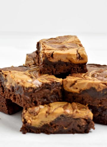 Stack of gluten free peanut butter brownies on parchment paper.
