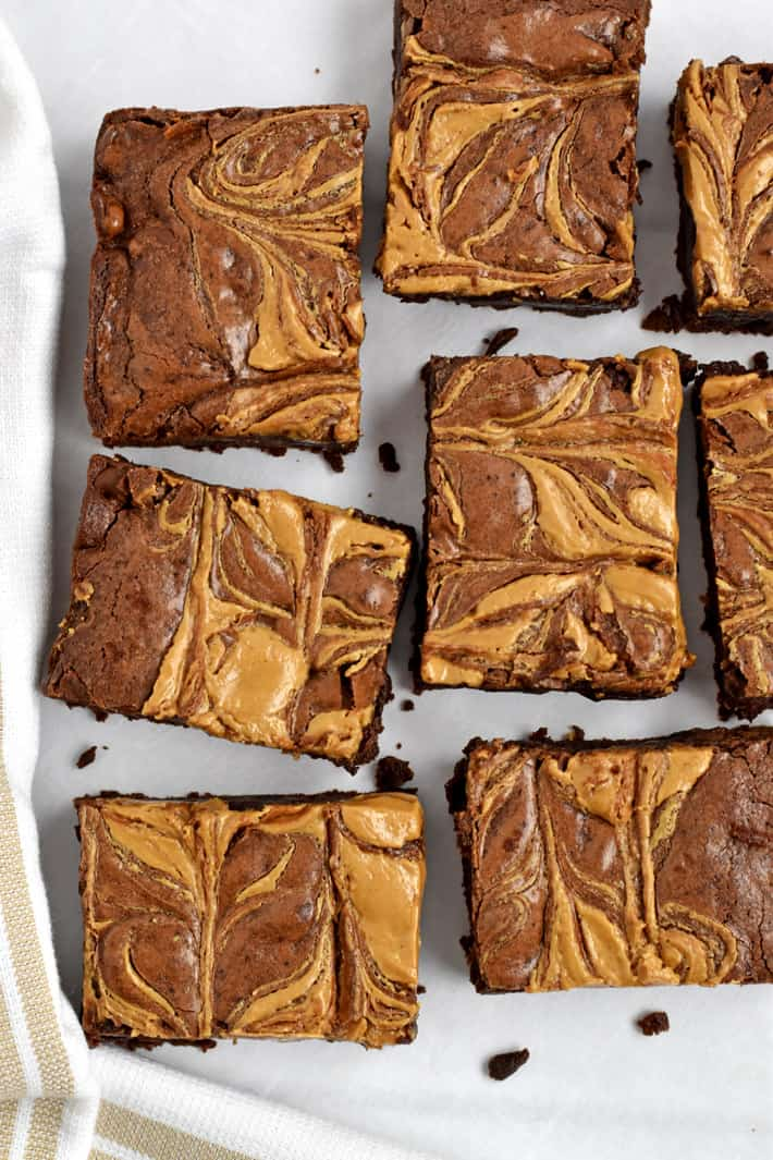 Overhead view of gluten free peanut butter brownies on parchment paper with kitchen towel in the lower left corner.