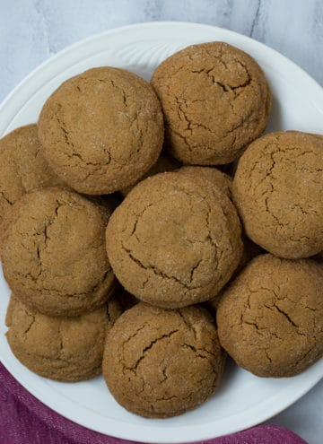 Overhead view of a stack of gluten free molasses cookies on a white plate with a rose colored kitchen towel in the bottom left corner.
