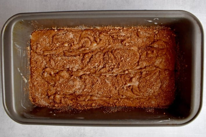 Overhead view of gluten free cinnamon bread batter in loaf pan after swirling the batter.