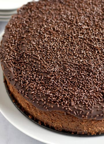 Close up view of an uncut chocolate brownie cheesecake on a round white plate with forks and smaller plates in the background.