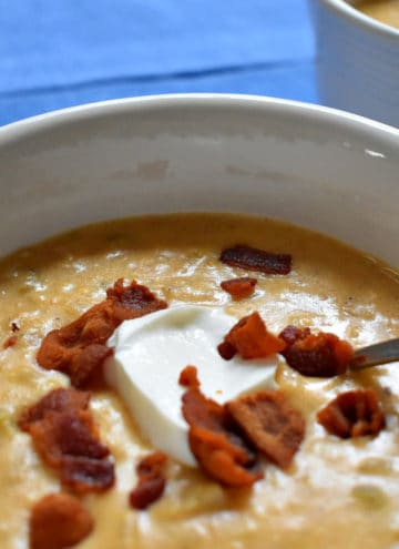 A white soup bowl filled with creamy cheese and potato soup garnished with bits of bacon and sour cream.