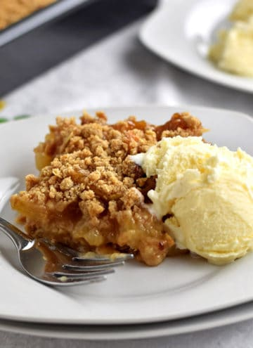 A slice of gluten free apple dessert with a scoop of vanilla ice cream and a fork on a stack of two white plates and more apple dessert in the background.