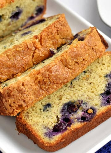 Slices of gluten free banana blueberry bread on a white rectangular plate placed on a blue kitchen towel.