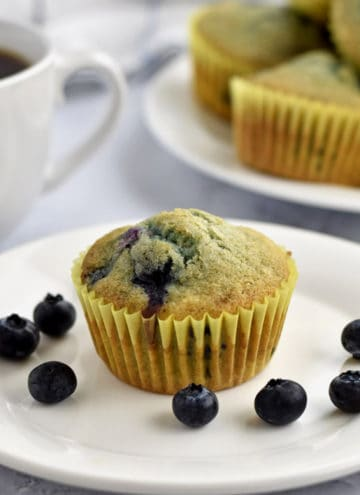 One gluten free blueberry muffin and some blueberries on a small white plate. A cup of coffee and more muffins in the background.