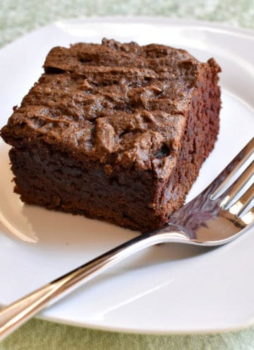 A slice of gluten free chocolate cake and a fork on a small white plate.
