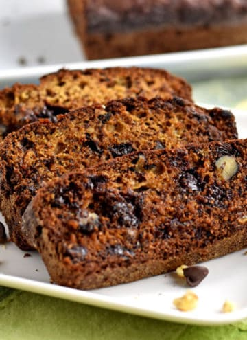 Three slices of gluten free chocolate chip banana bread and a few walnuts and chocolate chips on a square white plate with the remaining loaf in the background.
