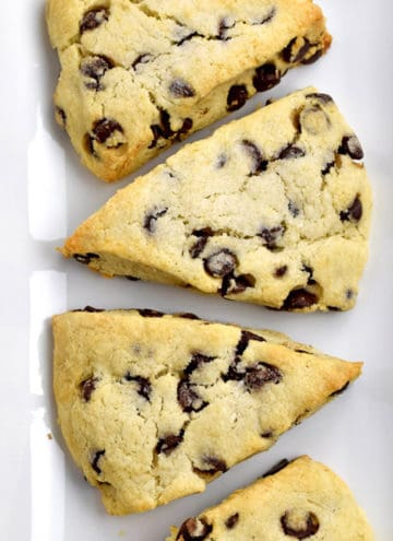 Overhead view of gluten free chocolate chip scones on a white rectangular plate.