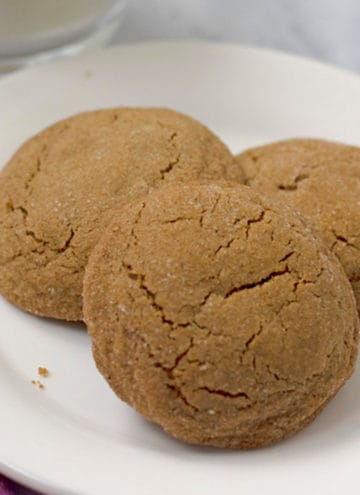 Three gluten free molasses cookies on a white plate with a glass of milk in the background.