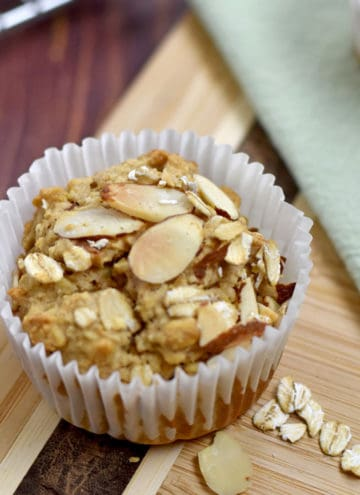 One gluten free oatmeal muffin on a brown cutting board with a few oats and slivered almonds on the cutting board.