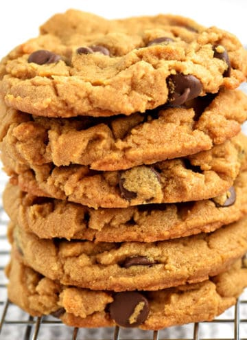 A stack of gluten free peanut butter chocolate chip cookies on a wire rack.