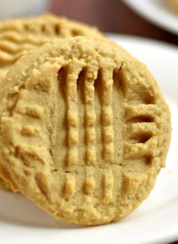 Close up of a gluten free peanut butter cookie propped against a stack of three more cookies on a white plate.