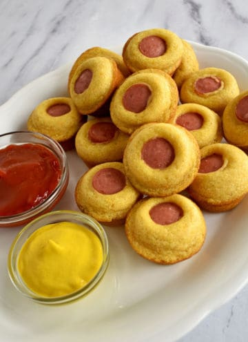 A white oval serving platter filled with mini corn dog muffins on a granite counter top . A small glass bowl of ketchup and a small glass bowl of yellow mustard are also on the platter.