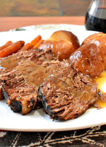 Three slices of slow cooker beef pot roast, red potatoes, and cooked carrots drizzled with gravy on a white dinner plate with a glass of red wine in the background.