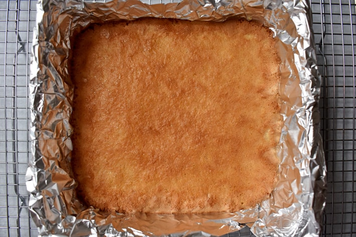 Overhead view of baked gluten free lemon bars in a foil-lined baking dish cooling on a wire rack.