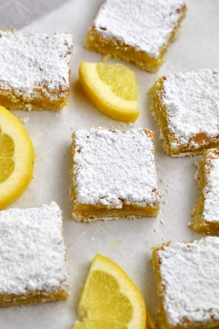 Close up view of a gluten free lemon bar with lemon slices and more lemon bars around it.