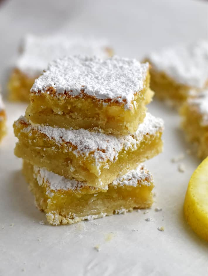 Close up view of a stack of three gluten free lemon bars on parchment paper with a lemon slice and more bars around the stack.