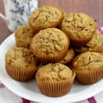 A stack of gluten free zucchini muffins on a round white plate with a blue and white decorative coffee cup in the background.