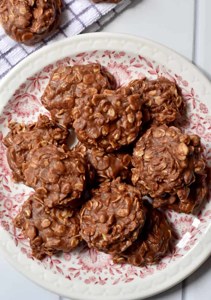 Overhead view of a stack of no bake cookies with chocolate chips on a pink and white plate with a purple and white striped kitchen towel and another cookie in the background.