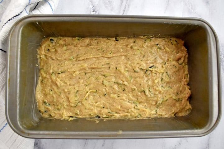 "Overhead view of gluten free zucchini bread batter in a 9x5"" loaf pan."
