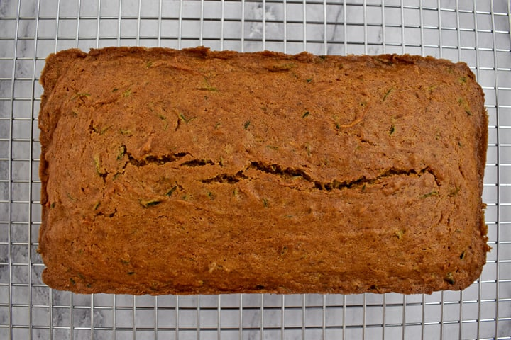 Overhead view of a loaf of baked gluten free zucchini bread cooling on a wire rack.
