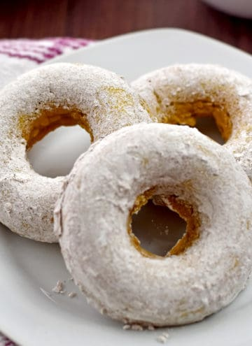 Three gluten free pumpkin donuts on a small white plate with a pink and white striped kitchen towel on the left.