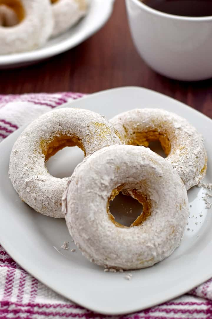 Three gluten free pumpkin donuts on a small white plate with a cup of coffee and a platter with more donuts in the background.