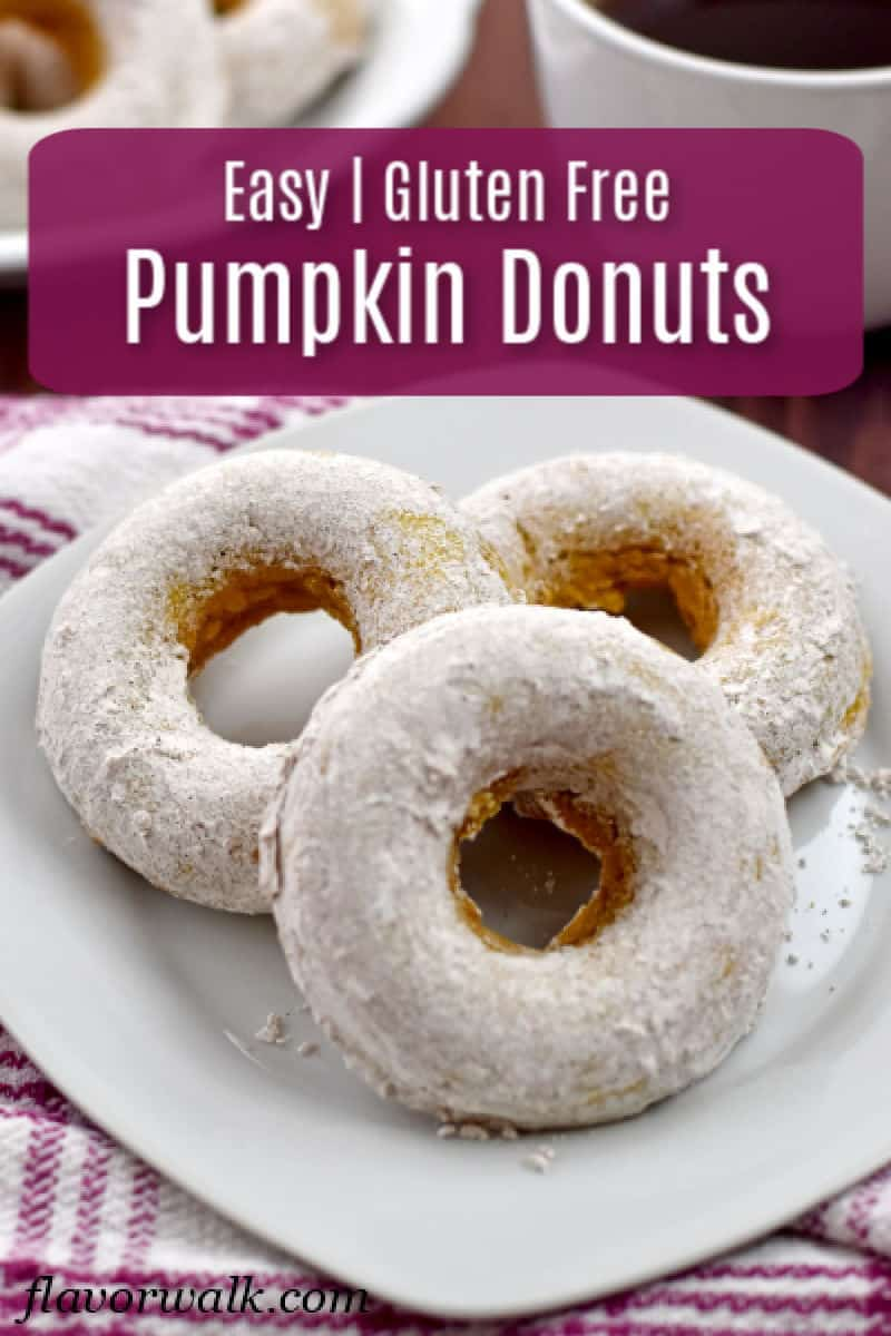 Three gluten free pumpkin donuts on white plate on top of a pink and white striped kitchen towel with a cup of coffee and platter of more donuts in the background. and a pink text overlay.