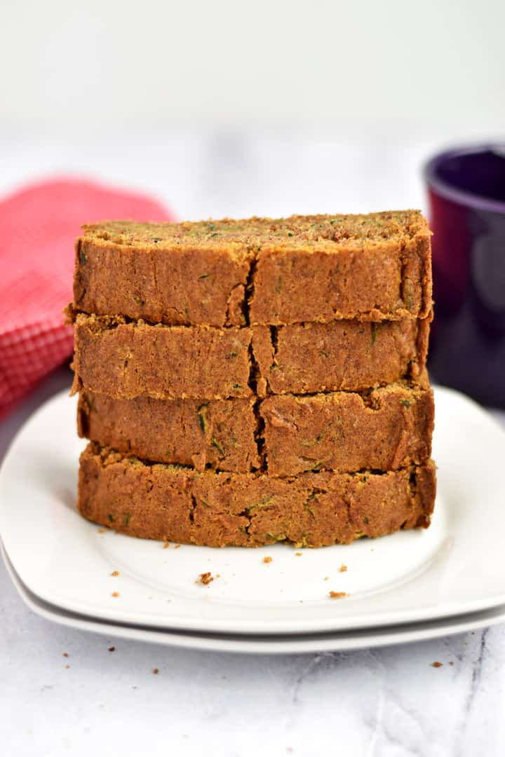 A stack of slices of gluten free zucchini bread on two white plates with a purple coffee mug and red and white checked kitchen towel in the background.