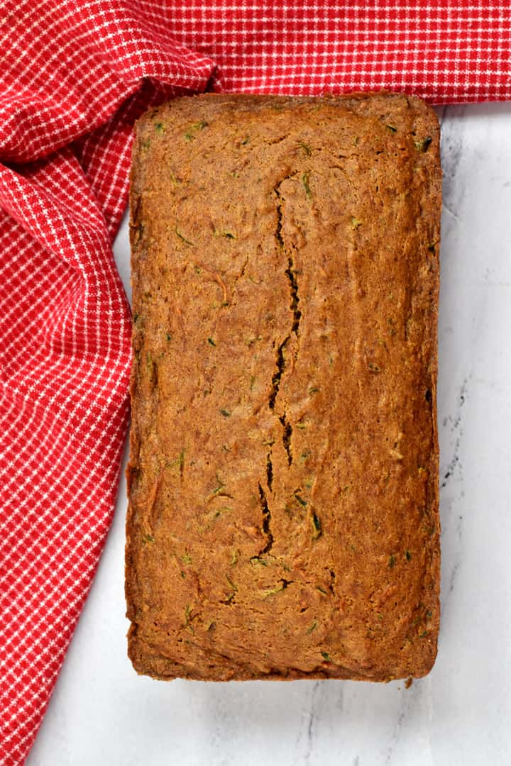 Overhead view of a loaf of baked gluten free zucchini bread on a kitchen counter with a red and white checked kitchen towel draped around the loaf.