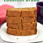 A stack of gluten free zucchini bread on two white plates, a purple mug and red and white checked towel in the background, and black and green text over lay at the top.