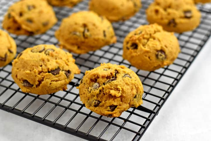 Baked gluten free chocolate chip pumpkin cookies cooling on a wire rack.