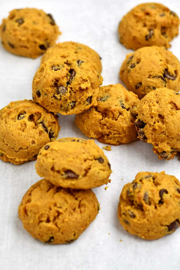 Gluten free chocolate chip pumpkin cookies scattered on parchment paper.