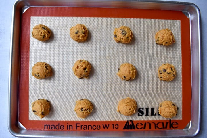 Overhead view of gluten free chocolate chip pumpkin cookie dough balls on a Silpat lined baking pan.